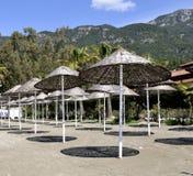 Hölzerner Matten-Regenschirm auf Strand Stockbilder