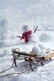 Hölzerner Pferdeschlitten und Schneebälle mit Schneemann Stockfotografie