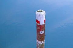 Hölzerner Pfosten mit einer Nr. 43 im Meer Stockfotos