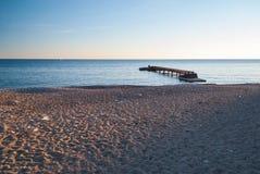 Hölzerner Pier auf dem leeren Strand bei Sonnenuntergang stockfotografie