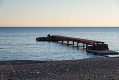 Hölzerner Pier auf dem leeren Strand bei Sonnenuntergang stockbilder