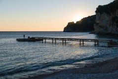 Hölzerner Pier auf dem leeren Strand bei Sonnenuntergang lizenzfreie stockfotos