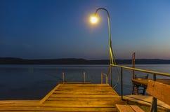 Hölzerner Pier auf dem See beleuchtete durch Lampe Lizenzfreies Stockfoto