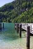 Hölzerner Pier auf einem See in den Alpen im Frühjahr gegen den Hintergrund von Bergen lizenzfreie stockfotografie