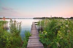 Hölzerner Pier auf großem See im Sommer Lizenzfreies Stockfoto