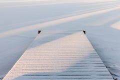 Hölzerner Pier bedeckt mit Schnee, Wintersee Lizenzfreies Stockbild