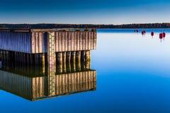 Hölzerner Pier, der über einen See nachdenkt Stockfotos