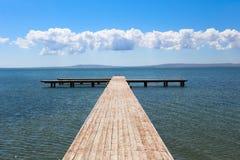 Hölzerner Pier, der in das Meer ausdehnt Lizenzfreie Stockfotografie