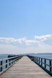 Hölzerner Pier, der in Ozean, dunstiger blauer Himmel sich ausdehnt Stockbild