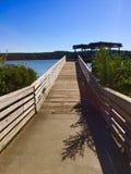 Hölzerner Pier, der zum See erlischt Stockfotos