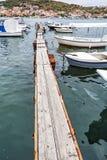 Hölzerner Pier mit Booten im Hafen, Trogir, Kroatien, vertikal Stockbilder