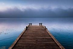 Hölzerner Pier nahe Nebelwolke im Morgenfluß stockfotografie