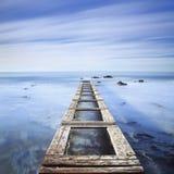 Hölzerner Pier oder Anlegestelle auf einem blauen Ozean morgens Langes Exposur Stockbild