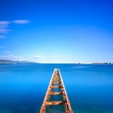 Hölzerner Pier oder Anlegestelle bleibt auf einem blauen Ozeansee Lange Berührung Lizenzfreie Stockbilder