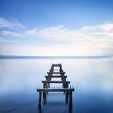 Hölzerner Pier oder Anlegestelle bleibt auf einem blauen See. Lange Belichtung. Stockfotografie
