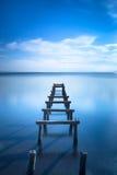 Hölzerner Pier oder Anlegestelle bleibt auf einem blauen See. Lange Belichtung. lizenzfreies stockfoto