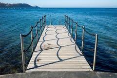 Hölzerner Pier zu einem Meer Stockfotos