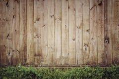 Hölzerner Plankenhintergrund, dunkle vertikale Bretter, hölzerne Beschaffenheit, alter Zaun und grünes Gras, Weinlese Lizenzfreies Stockfoto