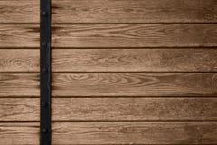 Hölzerner Plankenhintergrund mit schwarzer Metallstange Stockfotos