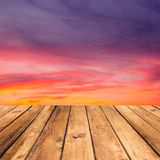 Hölzerner Plattformboden über schönem Sonnenunterganghintergrund. Lizenzfreies Stockbild