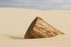Hölzerner Pole begraben im Sand Stockbild