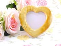 Hölzerner Rahmen des leeren Fotoherzens mit rosa Rosen und Geschenkbox auf süßer Blume Stockfotos