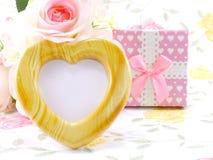Hölzerner Rahmen des leeren Fotoherzens mit rosa Rosen und Geschenkbox auf süßer Blume Lizenzfreies Stockbild