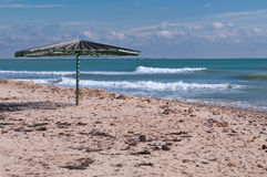 Hölzerner Regenschirm auf leerem Strand Stockbild
