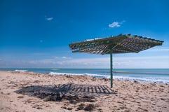 Hölzerner Regenschirm auf leerem Strand Lizenzfreie Stockfotos