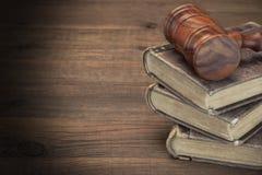 Hölzerner Richter-Hammer und alte Gesetzbücher auf Holztisch lizenzfreies stockfoto