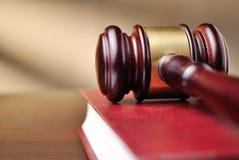 Hölzerner Richterhammer auf einem Gesetzbuch Stockbilder