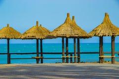 Hölzerner Ruheplatz mit Bänke im Strand mit staw Dach und blauem Meer, Himmel stockfoto