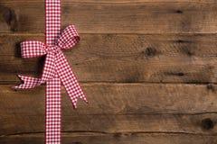 Hölzerner rustikaler Hintergrund mit einem roten weißen karierten Band Stockfotos