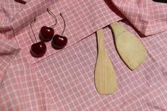 Hölzerner Schöpflöffel und Kirsche drei auf rosa Gitter Stoff Stockbilder