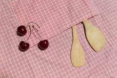 Hölzerner Schöpflöffel und Kirsche drei auf rosa Gitter Stoff Lizenzfreie Stockfotos