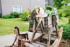 Hölzerner Schaukelpferdgartenpflanzer in der Nachbarschaft Lizenzfreie Stockfotos