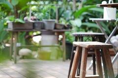 Hölzerner Schemel im grünen Garten Lizenzfreie Stockbilder