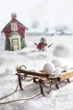 Hölzerner Schlitten und Schneebälle mit winterlichem Hintergrund Stockfotografie