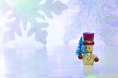 Hölzerner Schneemann auf Schneeflockenhintergrund Stockfotos
