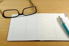 Hölzerner Schreibtisch mit Adressbuch, Stift und Lesebrille Stockbild