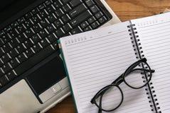 Hölzerner Schreibtisch mit Laptoptastatur, offenes Tagebuchbuch stockfotografie