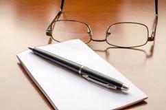 Hölzerner Schreibtisch mit Notizblock und Gläsern stockfotografie