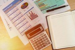 Hölzerner Schreibtisch mit offenem Tagebuchbuch und Datendiagramm Lizenzfreie Stockfotografie