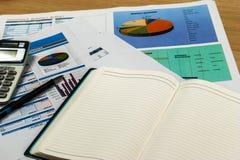 Hölzerner Schreibtisch mit offenem Tagebuchbuch und Datendiagramm Lizenzfreies Stockfoto