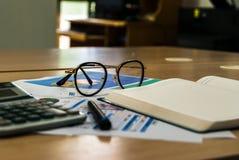 Hölzerner Schreibtisch mit offenem Tagebuchbuch und Datendiagramm Stockfotos