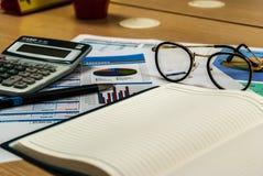 Hölzerner Schreibtisch mit offenem Tagebuchbuch und Datendiagramm Stockbild