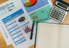 Hölzerner Schreibtisch mit offenem Tagebuchbuch und Datendiagramm Lizenzfreie Stockfotos