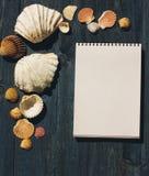 Hölzerner Schreibtisch mit Seeoberteilen und weißem Notizblock Stockfotos