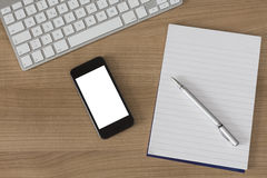 Hölzerner Schreibtischtastatursmartphone und -notizblock Stockbild