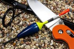 Hölzerner Schwimmer mit Angelrute und Messer aus den steinigen Grund Lizenzfreies Stockbild